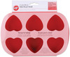 6 Cavity Heart 2.5 X2.5 X1.25  - Mini Silicone Mold WILTON-Six Cavity Silicone Baking mold: Heart.  These silicone molds are the perfect tool for molding cold foods: Jell-O, ice sculptures, Candies and hot foods: cake, muffins, cupcakes and so much more!  The flexibility makes removing foods much easier than your typical metal pans.  Great for freezer, refrigerator, oven (up to 500F/260C) and microwave use.  Dishwasher safe.  Stain and odor resistant.  Mold measures: 10-5/8x6-3/4x1-3/8in.  Color: Red. Imported.